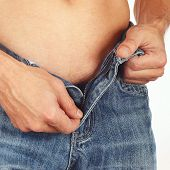 picture of unclothed  - Young man unzips blue jeans close up - JPG