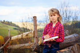 pic of grils  - Little artist gril with sketch in note at autumn landscape - JPG