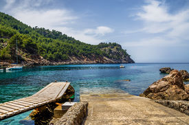 stock photo of promontory  - Launching ramp into the sea for small yachts and boats along side a wooden jetty with forest background on a promontory - JPG