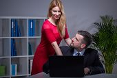 foto of inappropriate  - Sexy young woman courting her older employer at work - JPG