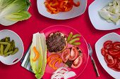 picture of hamburger  - Creating the perfect healthy hamburger with two grilled beef patties on buns with sliced fresh ingredients including sweet pepper dill cucumbers tomato lettuce and onion on a red background - JPG
