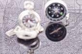 picture of reflection  - compass and a silver pocket watch on the background reflection maps - JPG