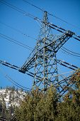 stock photo of transmission lines  - power mast of a high voltage transmission line in the mountains against blue sky - JPG