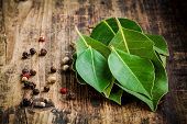 stock photo of bay leaf  - Fresh bay leaves peppercorns on a rustic wooden background - JPG