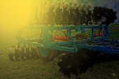 stock photo of cultivator-harrow  - Agricultural equipment in sunset light - JPG