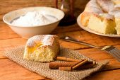 pic of curd  - Horizontal photo of Portion of curd cake together with cinnamon on jute cloth fork and bowl with powder sugar plus other portions in background - JPG