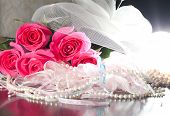 picture of garter  - Beautiful pink roses pearl beads and garter lying on a table - JPG