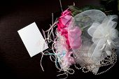 picture of garter  - Beautiful pink roses pearl beads and garter lie on a table near the note - JPG