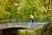 picture of rest-in-peace  - Mature couple leaning on railing of bridge resting during stroll in park - JPG
