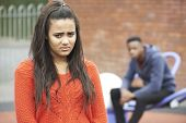 foto of conflict couple  - Portrait Of Unhappy Teenage Couple In Urban Setting - JPG
