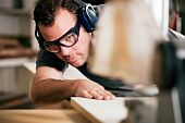 image of workplace safety  - Carpenter working on an electric buzz saw cutting some boards - JPG