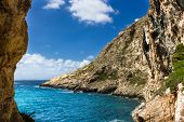 stock photo of gozo  - the rugged coastline of the island of Gozo are reflected in a blue sea - JPG