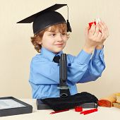 stock photo of conduction  - Little smiling boy in academic hat conducts scientific research with the microscope - JPG