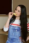 picture of overalls  - Brunette housewife wearing in blue denim overalls eating a slice of apple - JPG