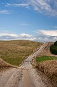 stock photo of dirt road  - Dirt road on a hill at spring time - JPG