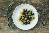 stock photo of olive branch  - A plate of Mediterranean olives in olive oil with a branch of olive tree and a small silver fork over a rough old wooden desk - JPG