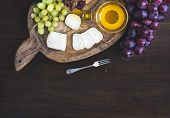 pic of brie cheese  - Goat brie cheese with fresh greapes and honey on a rustic wooden board over a dark wood background with a copy space - JPG