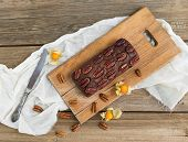 stock photo of ground nut  - Pecan brownie cake with ground cherry on a wooden board - JPG