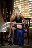 foto of black heel  - Attractive blonde woman in elegant long dress sitting near a table in a luxurious classic interior - JPG