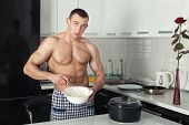 picture of pinafore  - Male bodybuilder knead the dough in the kitchen - JPG