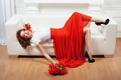 foto of yoke  - Girl in red dress lying on a white sofa and flirting - JPG