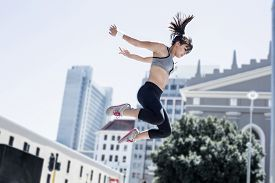 pic of parkour  - Woman doing parkour in the city on a sunny day - JPG