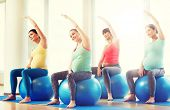 pregnancy, sport, fitness, people and healthy lifestyle concept - group of happy pregnant women exer poster