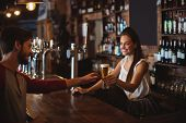 Female bar tender giving glass of beer to customer at bar counter poster