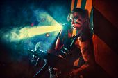 Young strong woman warrior with gun and flashlight in dramatic urban night scene poster
