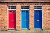 Three Differently Coloured Front Doors At The Entrance Of Old English Terraced Houses. Canterbury, E poster