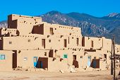 picture of pueblo  - Ancient Taos Pueblo with mountains on background - JPG