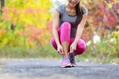 Running shoes woman runner tying shoe lace for run. Happy smiling girl getting ready for jogging lac poster