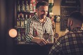 Man chatting with a bartender in a pub poster