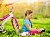 Bikes cycling kid girl. Child girl rides bicycle. Girl in cycling reading book near bicycle into par poster