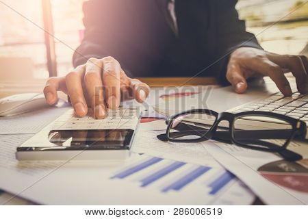 poster of Businessman Or Accountant Working On Calculator To Calculate Business Data Concept. Accounting,inves
