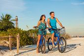 Florida beach vacation couple biking sport rental bikes recreational activity happy watching sunset  poster