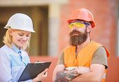 Safety Inspector Concept. Woman Inspector And Bearded Brutal Builder Discuss Construction Progress.  poster