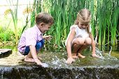 Happy Children Playing On Hot Summertime With Water In The Park poster