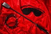 Bondage, Kinky Adult Sex Games, Kink And Bdsm Lifestyle Concept With A Whip, Collar, Eye Mask On Red poster