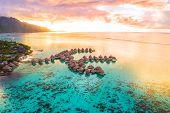 Luxury travel vacation aerial of overwater bungalows resort in coral reef lagoon ocean by beach. Vie poster