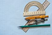 Mathematical instruments over the corner of a math graph paper with copy space for text. Math graphi poster