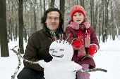stock photo of ruddy-faced  - Dad and daughter next to the snowman in winter forest - JPG