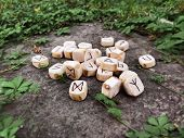 A Stack Of Wooden Runes At Forest. Wooden Runes Lie On A Rock Background In The Green Grass. Runes A poster