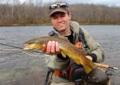 stock photo of brook trout  - A fly fisherman posing with a Brown Trout with his fly rod and reel - JPG