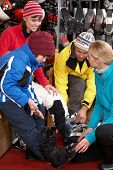 stock photo of ski boots  - Sales Assistant Helping Family To Try On Ski Boots In Hire Shop - JPG
