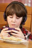 Boy Playing With Hand Held Games Console Whilst Eating Breakfast