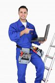 stock photo of osha  - Electrician pointing at his computer - JPG