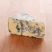 Close up of tasty blue cheese on the wooden surface