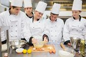 stock photo of pastry chef  - Pastry chef showing students how to prepare dough in kitchen - JPG