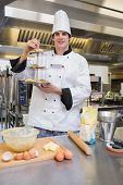 pic of flour sifter  - pastry chef presenting tiered cake tray with cupcakes in kitchen - JPG